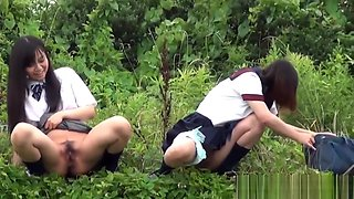 Asian teenagers peeing in bushes