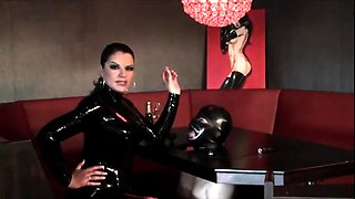 Sexy babe in latex enjoys a cigarette and punishes her slave