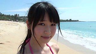 Slim Asian girl Tsukasa Arai walks on a sandy beach under the sun