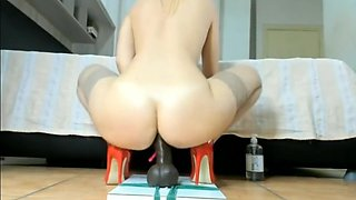 Blonde in stockings and high heels rides a big black dildo
