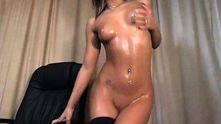 Oiled brunette fingers her pussy