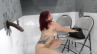 Redhead Amber awarding dick with blowjob through gloryhole