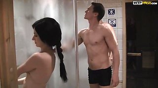 Beautiful brunette with tiny tits is kneeling in the shower and sucking two rock hard dicks