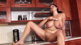 A plump chick is in the kitchen and she is playing with her large boobs